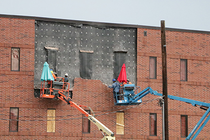 Two crews begin the process of clearing bricks from the outside of TWHS for the new wing.