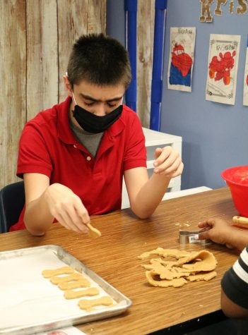 A student works to shape dog treats in the classroom.